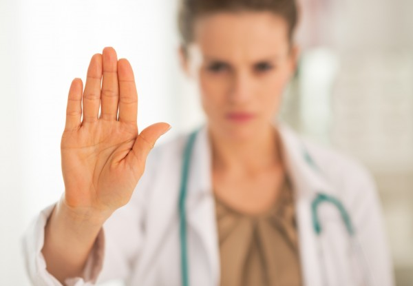 Closeup on serious medical doctor woman showing stop gesture