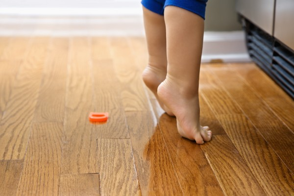 Feet of Caucasian toddler boy with magnets in front of refrigera